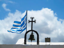 The Greek National flag near cross of small church against blue Stock Photo