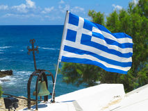 The Greek National flag near cross of small church against blue Royalty Free Stock Image