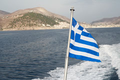 Greek national flag at sea waves and island Stock Images