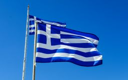 Flags of Greece Flying in Wind and Blue Sky Royalty Free Stock Images