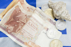 Greek old currency drachma banknotes and a shell on the Greek fl Royalty Free Stock Photo