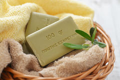 Greek olive soap. With bath towels and olive twig in basket closeup Royalty Free Stock Photography
