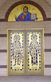 Greek Orthodox Icon Arch & Saints On Doors. Greek Orthodox Arch Mosaic Icon of a Religious Saint Above Gold, Red, Blue and Yellow Stained Glass Saints Royalty Free Stock Images