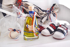 Greek Orthodox christening objects - baby shoes, baptism oil, soap and candles royalty free stock photo
