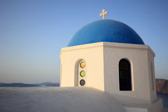 Greek orthodox church. Traditional Greek white church arch with cross and bells in village Oia of Cyclades Island Santorini Greece Stock Photo