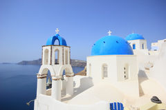 Greek orthodox church. Traditional Greek white church arch with cross and bells in village Oia of Cyclades Island Santorini Greece Royalty Free Stock Photo