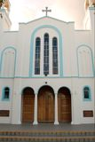 Greek Orthodox Church. Front with white walls, wooden doors and a brooding sky royalty free stock photo