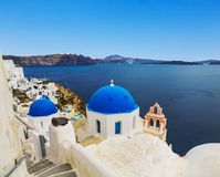 The Greek Orthodox Church on the background waters of the Aegean sea in Oia town on Santorini island. In Greece Stock Photography