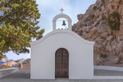 Greek Orthodox Church with brown door in Rhodes island with blue sky. And little clouds in the background Royalty Free Stock Image