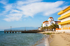 Greek orthodox Church in Paralia Katerini beach, Greece. Greek orthodox Church in Paralia Katerini, wooden pier, palm trees and sandy beach, Greece Stock Images