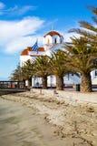 Greek orthodox Church in Paralia Katerini beach, Greece. Greek orthodox Church in Paralia Katerini, wooden pier, palm trees and sandy beach, Greece Stock Photo