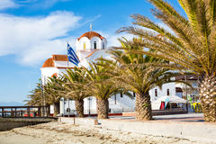 Greek orthodox Church in Paralia Katerini beach, Greece. Greek orthodox Church in Paralia Katerini, wooden pier, palm trees and sandy beach, Greece Stock Image