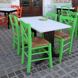 Greek outdoor cafe with green wooden chairs, Crete, Greece royalty free stock photos