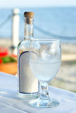 Greek ouzo. Drink in front of the coast Stock Photos