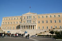 Greek Parliament, Athens. The building of the Greek parliament in Athens. People are watching the traditional guards (evzones royalty free stock photos