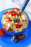 Greek Pasta Salad. Bowl of greek orzo pasta salad on blue serveware Royalty Free Stock Images