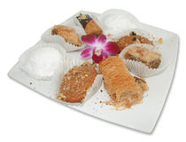 Greek Pastries With Flower. A square plate of Greek pastries in paper cups Royalty Free Stock Image