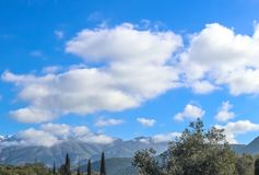 Greek Peloponnese Mountains with snow and cloud covered peaks in the distance under blue cloudy sky with olive and Cypress trees. In the foreground - selective royalty free stock photo