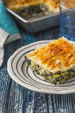 Greek pie spanakopita in the white plate on the blue wooden table Royalty Free Stock Images