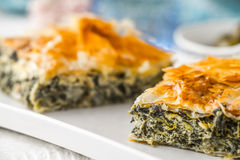 Greek pie spanakopita on the white plate with blurred accessorizes horizontal. Greek pie spanakopita on the white plate on the white wooden table with  blurred Royalty Free Stock Image