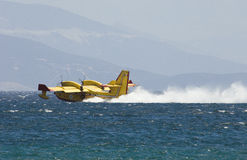 Greek pilot collects water to drop on fires. Fire fighting plane collecting water in sea off Athens Stock Images