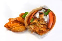 Greek pork gyros sandwich junk food meat meal. Greek pork gyros sandwich in pie with onion potatoes tomatoes and red and yellow sauce Stock Image