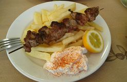 Greek pork souvlaki. And chips. Yogurt on side. Lemon wedge. Paprika. Taverna food Stock Images