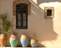 Greek pots. Colourful pots in the traditional Cretan style, outside a house in Rethymno. The stone window surrounds are typical of the old stone-built houses Stock Photo