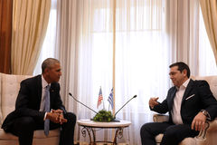 Greek Prime Minister Alexis Tsipras, right, speaks with U.S. Pre Royalty Free Stock Photo