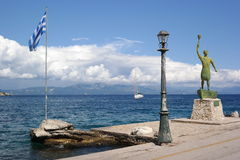 Greek promenade. Greek flag male statue and lamppost promenade against blue sea and sky with white clouds boat sunny day Royalty Free Stock Photo