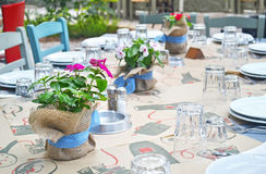 Greek restaurant table with blooming flowers Stock Photos