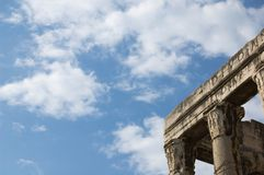 Greek ruins. Ruins of a classic Greek building with blue sky and cloud background Stock Image