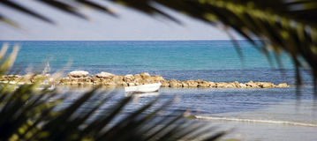 Greek Sail Boat. Little white boat viewed through palms royalty free stock photo