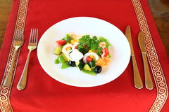 Greek salad. Table in the restaurant served up cutlery and put a dish with a Greek salad Royalty Free Stock Photos