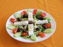 Greek salad. A plate or dish of light, refreshing Greek salad on an orange tablecloth stock photos