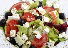 Greek salad. Close up with feta cheese, tomatoes, olives and green leafs Stock Photos