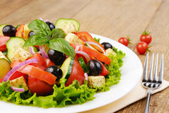 Greek salad. In the white plate on the kitchen table Stock Photography