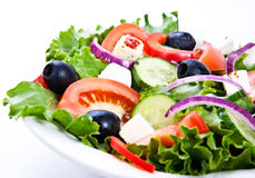 Greek salad. A plate with green salad leafes, cucumber, feta,red onion and olives Stock Photos