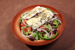 Greek salad. On plate and feta cheese on top Royalty Free Stock Images