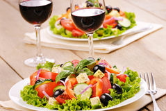 Greek salad. And glasses of red wine Royalty Free Stock Photography