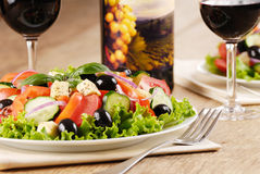 Greek salad. And glass of red wine on the oak table Stock Photo