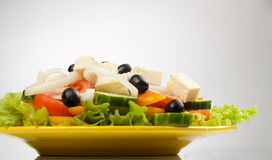 Greek Salad. On white background in yellow plate Royalty Free Stock Photography