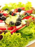 Greek salad. With fresh lettuce leaves, tomato, cucumber, feta, olives, pepper, and lime royalty free stock photography