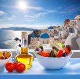 Greek salad against famous church in Oia village, Santorini island in Greece stock photos