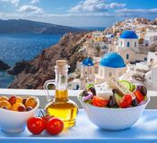 Greek salad against famous church in Oia village, Santorini island in Greece. Greek salad against famous church in famous Oia village, Santorini island in Greece royalty free stock images