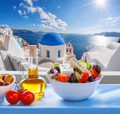 Greek salad against famous church in Oia village, Santorini island in Greece royalty free stock photography