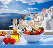 Greek salad against famous church in Oia village, Santorini island in Greece royalty free stock photo