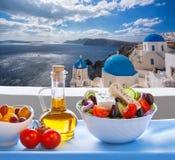 Greek salad against famous church in Oia village, Santorini island in Greece stock photography