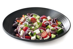 Greek Salad on Black Plate Side View Isolated on white Royalty Free Stock Image