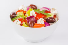 Greek salad in a bowl. Fresh vegetable salad isolated on a white Stock Photography